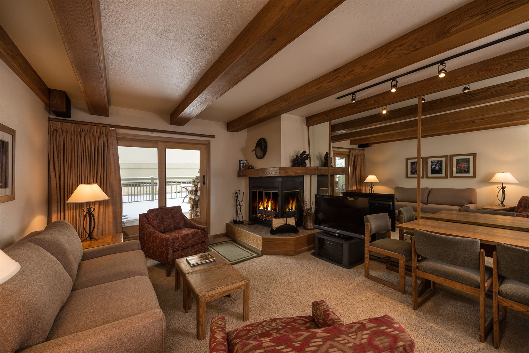 2BGold_Living room with corner fireplace and dining table
