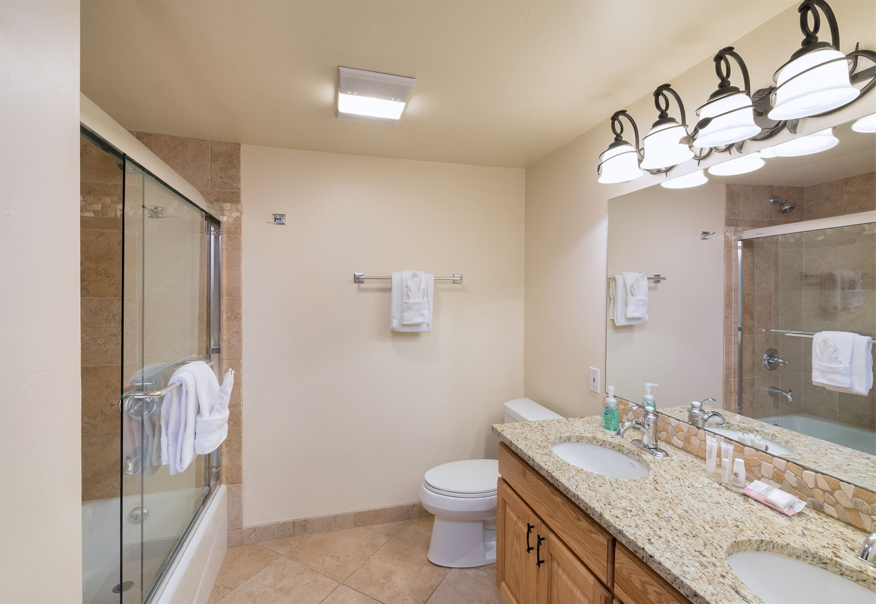 2BGold_View of bathroom with dual sinks and standing shower on opposite wall with toilet beside the sink