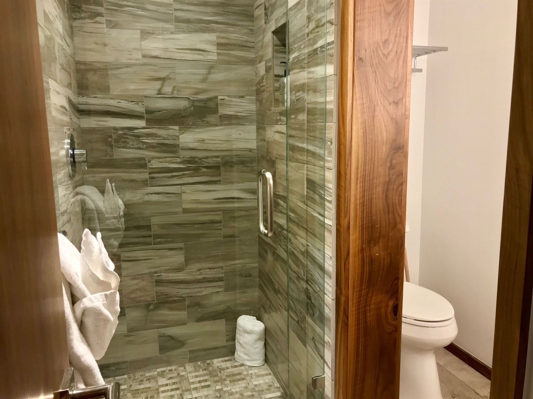 Bathroom with standing shower and toilet beside it