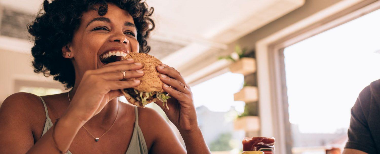 Woman Eating Burger at Hip Restaurant